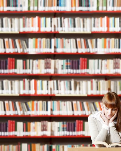 Portrait of a serious young student reading a book in a library